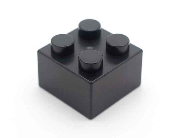 Schwarzer Legostein als Beispiel für Masterbatch Compounder von BUSS