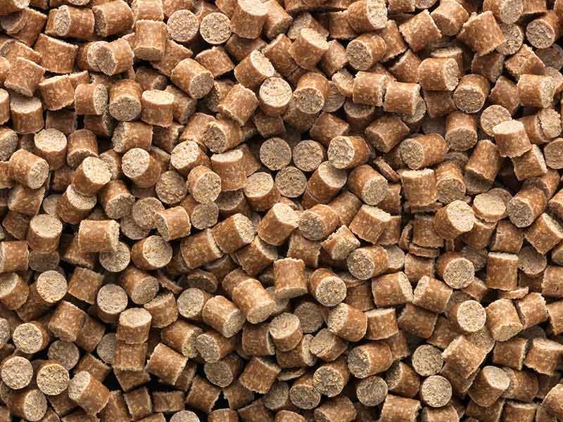 Trozos de masa en bruto de color marrón de material compuesto de fibras naturales, procedente de un equipo de preparación de compuestos de BUSS